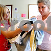 Rob Winner – rwinner@daily-chronicle.com<br /> <br /> Volunteers Bethany Billips, 10, and her mother Becky Billips of the Blessing Well of the First Church of the Nazarene in DeKalb, Ill. help bag a clients clothing items on Wednesday August 11, 2010.