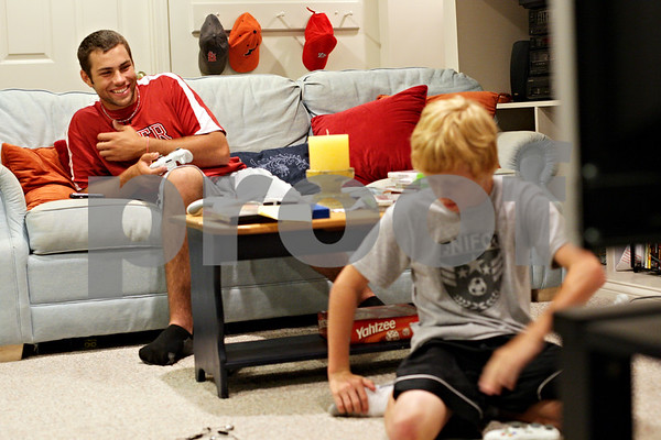 Beck Diefenbach  -  bdiefenbach@daily-chronicle.com<br /> <br /> DeKalb County Liners third baseman Adam Wayman (left) relishes in his victory over Adam Millburg, 13, at Millburg's home in Sycamore, Ill., on Monday August 2, 2010. Wayman, of Rider University in New Jersey, has been staying with the Millburg family while he plays for the summer collegiate league team.