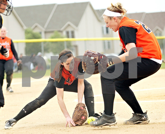 Beck Diefenbach  -  bdiefenbach@daily-chronicle.com<br /> <br /> Neither DeKalb pitcher Tia Lexa (5, left) and Mackenzie Johnson (21, right) can get control of a bunt during the third inning of the game against Sycamore at Sycamore High School in Sycamore, Ill., on Monday May 10, 2010.