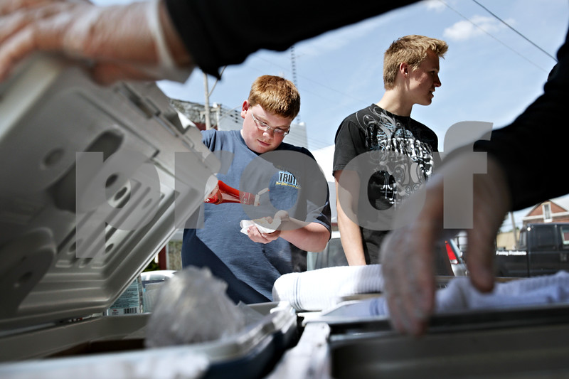 Beck Diefenbach  -  bdiefenbach@daily-chronicle.com<br /> <br /> Genoa-Kingston High School students John McNeely (left) and Brent Jacobson get their free hot dogs from the Patriots Hot Dog stand in Malta, Ill., on Monday April 26, 2010. McNeely and Jacobson were among many students in the building trades class which received free hot dogs for completing the construction of the new Malta police department.