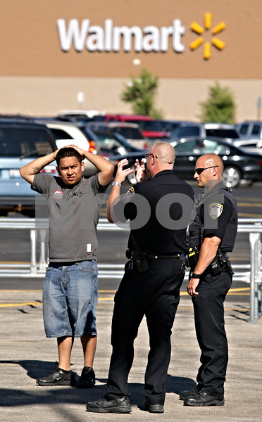 Beck Diefenbach  -  bdiefenbach@daily-chronicle.com<br /> <br /> Angel Garcia, of DeKalb, talks with DeKalb police officers as firefighter put out the flames which destroyed his Lincoln Aviatior in the Walmart parking lot in DeKalb, Ill., on Friday July 2, 2010.