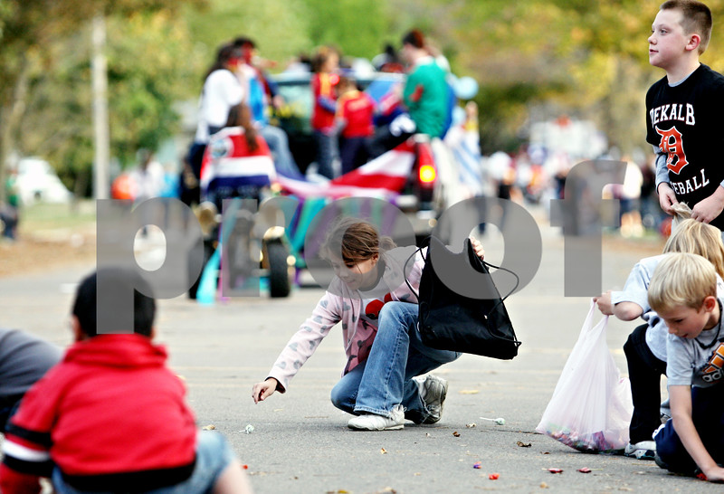 Rob Winner – rwinner@daily-chronicle.com<br /> <br /> 10-year-old Lily Jones collects candy on Second Street as the DeKalb High School homecoming parade marches by on Thursday October 14, 2010 in DeKalb, Ill.