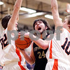 Beck Diefenbach - bdiefenbach@daily-chronicle.com<br /> <br /> Sycamore's Harlan Johnson (24, center) plows through DeKalb's Jake Jouris (32, left) and Chris Calbow (10, right) during the second quarter of the IHSA Class 3A regional semifinal game against Sycamore at Kaneland High School in Maple Park, Ill., on Tuesday March 2, 2010.