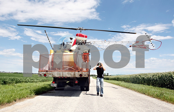 Rob Winner – rwinner@daily-chronicle.com<br /> <br /> A helicopter piloted by Ron Smith, of Hendrickson Flying Service located in Rochelle, lands on top of a truck to get a refill of fungicide while spraying farm fields near Fenstermaker and Barber Greene roads in Cortland Township on Friday July 23, 2010.