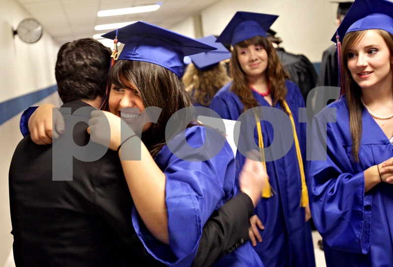 Beck Diefenbach  -  bdiefenbach@daily-chronicle.com<br /> <br /> Genoa-Kingston High School senior Nasya Ramirez (center) hugs school band director Michael Lipinski before the graduation ceremony at G-K High School in Genoa, Ill., on Tuesday May 18, 2010.