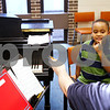 Beck Diefenbach  -  bdiefenbach@daily-chronicle.com<br /> <br /> Nicholas Chen, 8, of DeKalb, Ill., tries to remember which notes are which on his sheet music with the help of his teacher Quentin Dover (far right) during a guitar basics lesson at the Northern Illinois University Community School of Music in DeKalb, Ill., on Wednesday March 17, 2010.