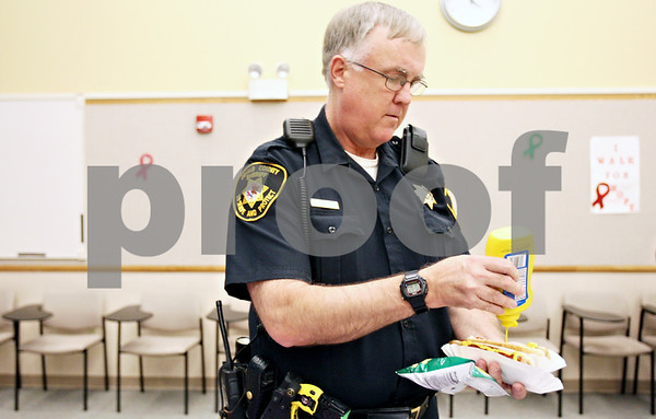 Rob Winner – rwinner@daily-chronicle.com<br /> <br /> Deputy Ray Nelson tops off his hot dogs with mustard during a Relay for Life fundraiser at the DeKalb County Government Legislative Center in Sycamore, Ill. on Wednesday May 26, 2010.