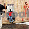 "Beck Diefenbach - bdiefenbach@daily-chronicle.com<br /> <br /> Jay Allen (center), of Shaw Craft Sign Company, prepares to assemble a mural on the exterior of the Genoa Public Library with the help of Joe Marshall (left) in Genoa, Ill., on Monday March 8, 2010. The mural recognized Genoa's role in the ""Good Roads Movement."""