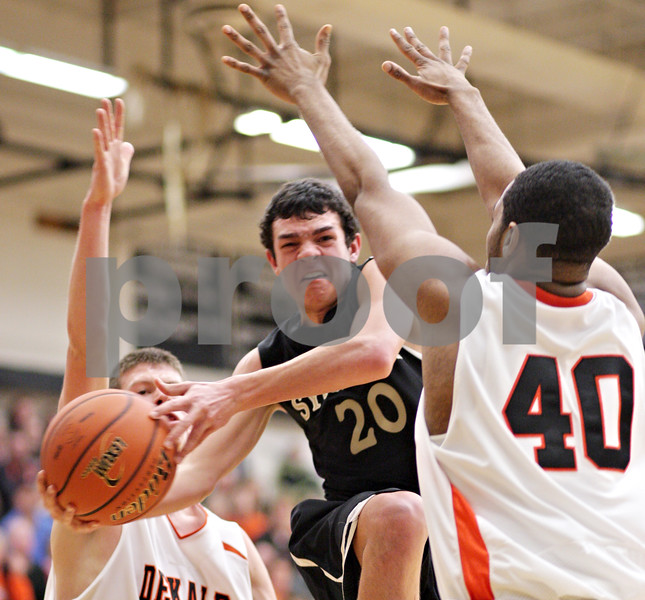Beck Diefenbach - bdiefenbach@daily-chronicle.com<br /> <br /> Sycamore's Josh Reed (20, center) tries to pass the ball around DeKalb's Craig Lane (40, right) during the second quarter of the IHSA Class 3A regional semifinal game at Kaneland High School in Maple Park, Ill., on Tuesday March 2, 2010.