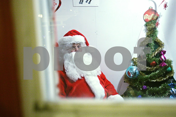 Rob Winner – rwinner@daily-chronicle.com<br /> <br /> Santa Claus waits in his house in front of the DeKalb County Courthouse on Friday night in Sycamore.