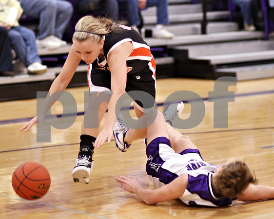 Beck Diefenbach  -  bdiefenbach@daily-chronicle.com<br /> <br /> DeKalb's Kay Smith (13, top) knocks over Hampshire's Michelle Dumoulin (13, bottom) during the second quarter of the IHSA Class 3A Regional championship game at Rochelle Township High School in Rochelle, Ill., on Thursday Feb. 18, 2010.