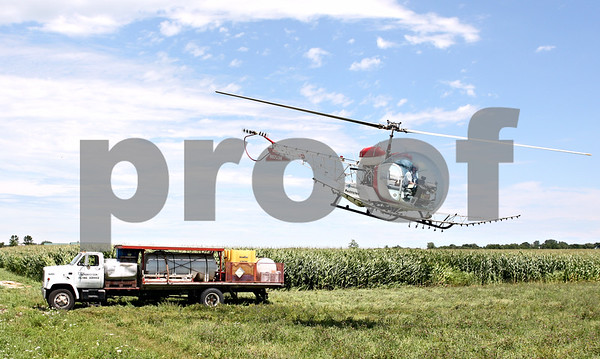 Rob Winner – rwinner@daily-chronicle.com<br /> <br /> A helicopter piloted by Ron Smith, of Hendrickson Flying Service located in Rochelle, takes off from the top of a truck while spraying farm fields near Fenstermaker and Barber Greene roads in Cortland Township on Friday July 23, 2010.