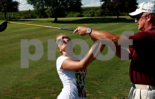 Beck Diefenbach - bdiefenbach@daily-chronicle.com<br /> <br /> Indian Creek girls golf coach Keith Haeg (right) works with sophomore Virginia Fillicetti on her swing during practice at the Indian Oaks Golf Course in Shabbona, Ill., on Wednesday Aug. 18, 2010.