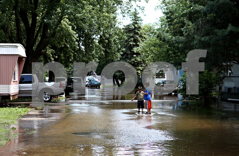 Rob Winner – rwinner@daily-chronicle.com<br /> <br /> Two boys find a dry spot on a flooded street within Evergreen Village in Sycamore, Ill. on Saturday July 24, 2010.