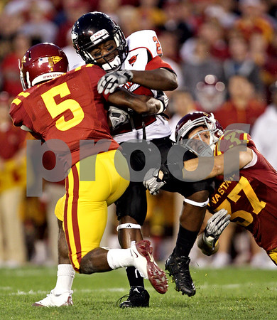 Beck Diefenbach  -  bdiefenbach@daily-chronicle.com<br /> <br /> Northern Illinois's Ricky Crider (22, center) is tackled by Iowa State's Jeremy Reeves (5, left) and Ben Dinkins (37, right) during the second quarter of the game at Jack Trice Stadium on the campus of Iowa State University in Ames, Iowa, on Thursday Sept. 2, 2010.