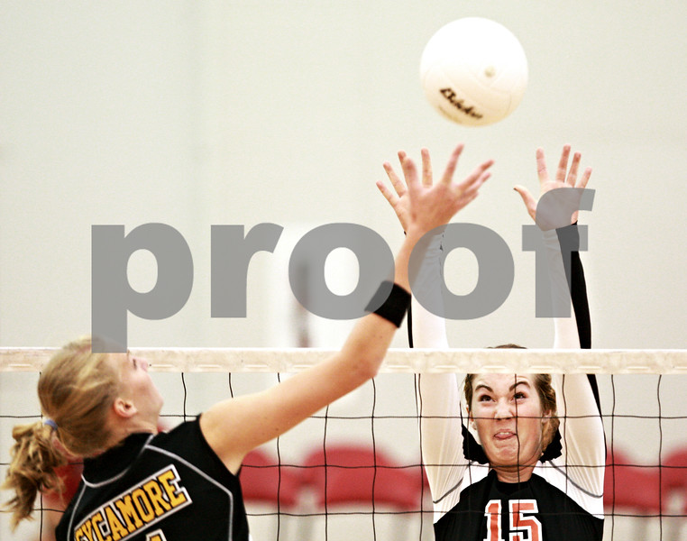 Beck Diefenbach – bdiefenbach@daily-chronicle.com<br /> <br /> DeKalb's Emily Bemis (15, right) attempts to block a shot by Sycamore's Envy McCoy (11) during the first game of the match at Victor E. Court in the Convocation Center on the campus of Northern Illinois University in DeKalb, Ill., on Tuesday Sept. 14, 2010. DeKalb defeated Sycamore 2 to 1.