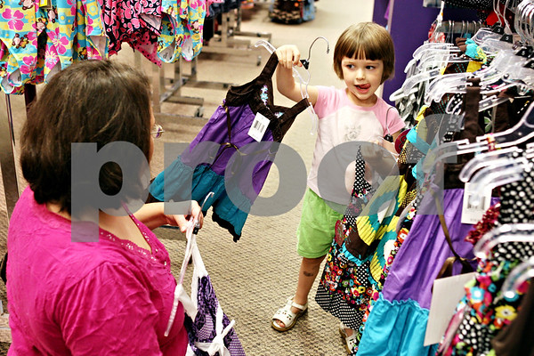 Rob Winner – rwinner@daily-chronicle.com<br /> <br /> Jeanette Johnson, of DeKalb, looks at a dress that her 3-year-old daughter, Hope, picked from one of the racks at JCPenney in DeKalb, Ill. on Friday August 6, 2010. The sales tax holiday was a reason why the Johnson family went clothes shopping on Friday.