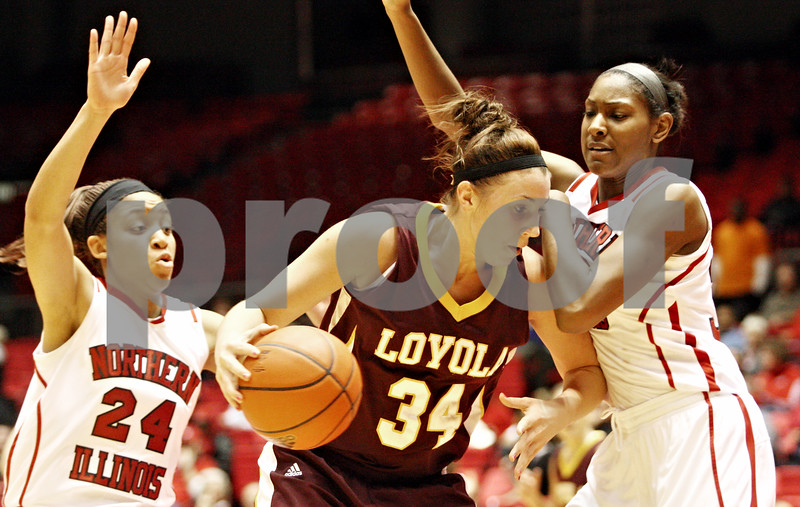 Rob Winner – rwinner@daily-chronicle.com<br /> <br /> Northern Illinois forward Kim Davis (24) and forward Shaakira Haywood pressure Loyola forward Abby Skube on her way to the basket during the first half in DeKalb, Ill. on Tuesday, Dec. 28, 2010.