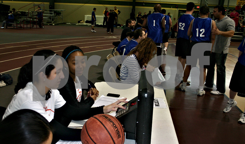 Dana Herra dherra@daily-chronicle.com<br /> <br /> DeKalb High School sophomores Rachel Torres, left, and Courtney Patrick run the scoreboard and keep statistics Sunday afternoon during a Special Olympics basketball tournament at the Sycamore High School field house. The girls were among 16 DHS basketball players who volunteered at the tournament.