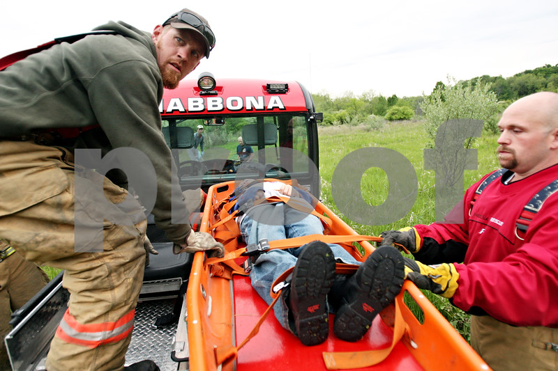 Beck Diefenbach  -  bdiefenbach@daily-chronicle.com<br /> <br /> Firefighters Tim Parrish (left) and Joe Duetsch load Logan Breese into the back of a truck during weekly training at Shabbona State Park in Shabbona, Ill., on Monday May 18, 2010.