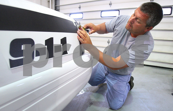 Kyle Bursaw – kbursaw@daily-chronicle.com<br /> <br /> Johnn Lucius, a sign technician for the city of DeKalb, takes a measurement as he lines up a decal for one of five new police squad cars on Wednesday, May 25, 2011.