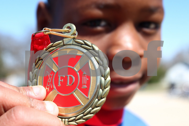Kyle Bursaw – kbursaw@daily-chronicle.com<br /> <br /> My'Kel Childs holds up the medal he was awarded by the DeKalb Fire Department on Wednesday, May 4, 2011 during an assembly at Littlejohn Elementary school. Childs came home to find his kitchen on fire and woke up his mother by banging on her window.