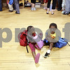 Rob Winner – rwinner@daily-chronicle.com<br /> <br /> 4-year-old Breasia Burton and her cousin Anton Brooks, 4, both of DeKalb, sit on the floor at Conexion Comunidad during the sixth annual Back to School Fair on Thursday night in DeKalb. Children received a free book bag and school supplies. Free vision screenings and immunizations were also available.