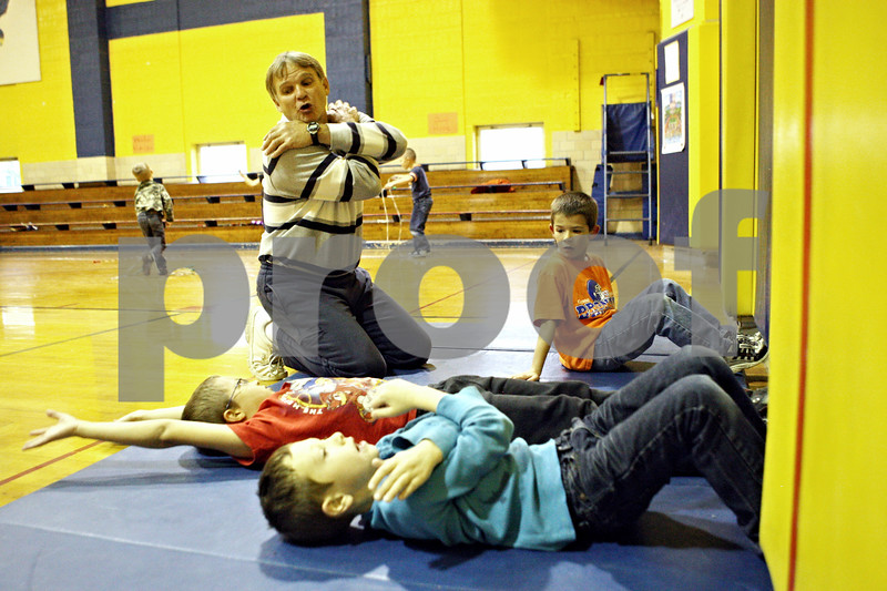 Rob Winner – rwinner@shawmedia.com<br /> <br /> Hiawatha Elementary students Matthew Dyson (from front to back), 7, Nathaniel Velazquez, 7, and Kurtis Ruegsegger, 6, listen to physical education instructor Dave Cox while doing sit-ups on Thursday, Nov. 3, 2011. The Kirkland school has for the second time in three years been named state champion in its division in the President's Council of Physical Fitness competition.