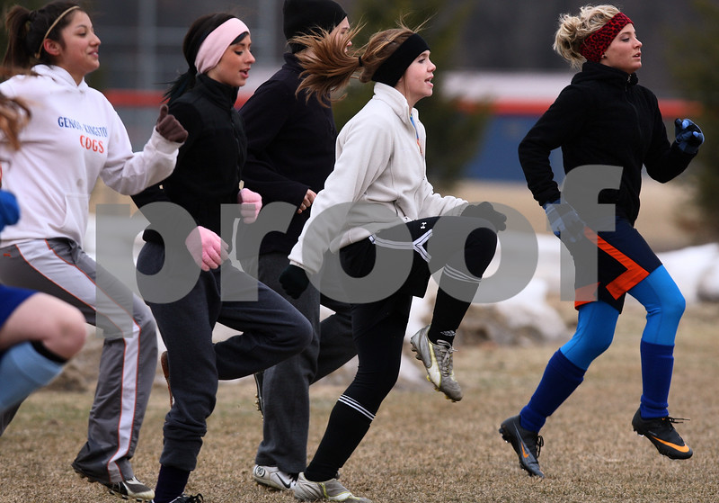 Kyle Bursaw – kbursaw@daily-chronicle.com<br /> <br /> Genoa-Kingston's Shannon Schumacher (center) and teammates do high knees to warm up at soccer practice on Tuesday, March 8, 2011.