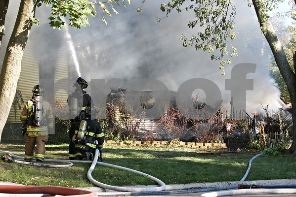Rob Winner – rwinner@shawmedia.com<br /> <br /> Fire fighters work to extinguish a fire at a house located on the 200 block of South Genoa Street in Genoa on Wednesday afternoon.