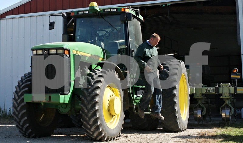 Rob Winner – rwinner@shawmedia.com<br /> <br /> Mike Schweitzer of Schweitzer Farms in Malta hops down from a tractor as his family begins preparing for the upcoming harvest on Thursday, Sept. 15, 2011.