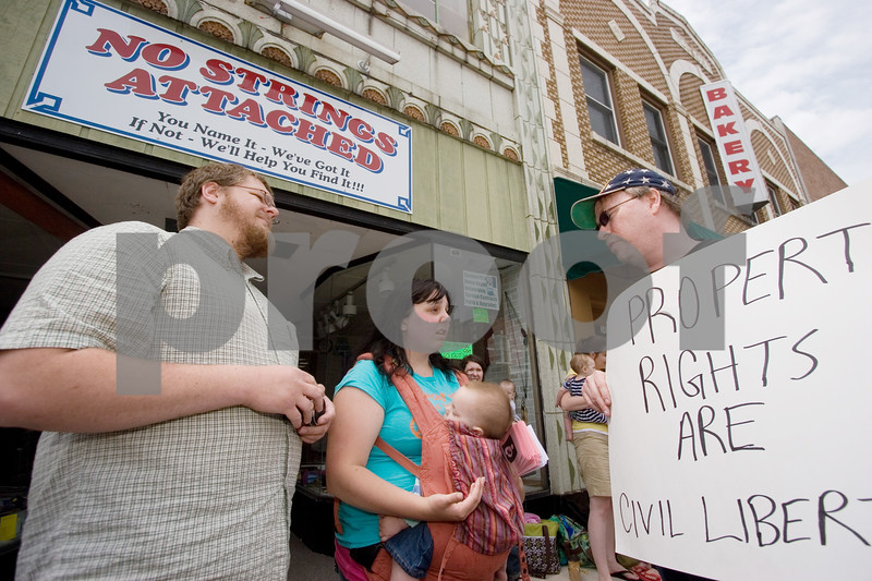 """Curtis Clegg - cclegg@shawsuburban.com<br /> <br /> Nichole Eidsmoe (center) and self-proclaimed """"libertarian activist"""" Ted McCarron (right), both of DeKalb, get into a heated discussion about the legalities of breast feeding in public places in front of the No Strings Attached resale shop in DeKalb on Thursday, June 2, 2011. Eidsmoe claims she was asked not to breast feed her daughter in the shop on Tuesday.  At left is Eidsmoe's fiance John Ehle, also of DeKalb."""