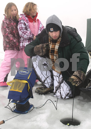 Kyle Bursaw – kbursaw@daily-chronicle.com<br /> <br /> Ryon Ubert puts a camera into the opening in the ice to look for fish as Violet Worel (left) and Sera Dalki (center) look over his shoulder. Ubert was ice fishing on Shabbona Lake on Thursday, Dec. 30, 2010.