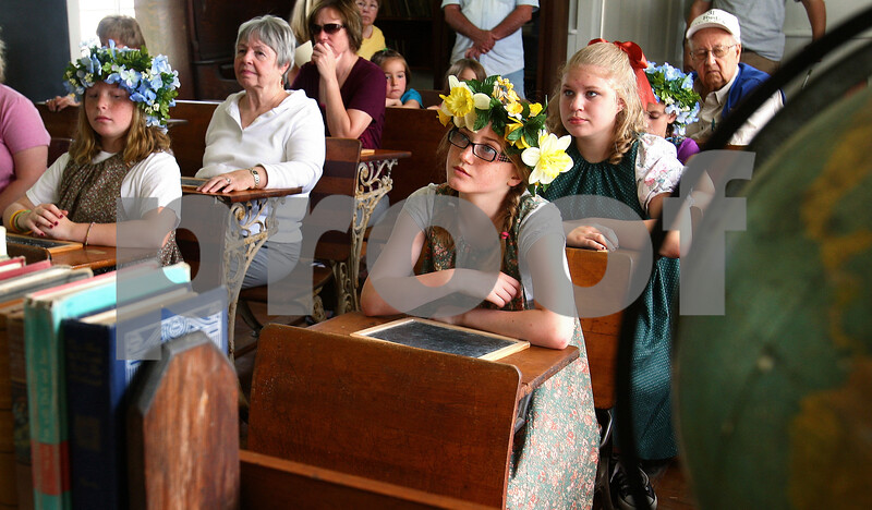 Kyle Bursaw – kbursaw@daily-chronicle.com<br /> <br /> Libby Swedberg (front and center) and others listen to a speech about about North Grove, the one room schoolhouse they are in. Swedberg and a few other girls including Riley Herrmann (far left) and Rebecca Roby (second row) wore period costumes for the North Grove Fun Fair on Saturday, June 25, 2011.