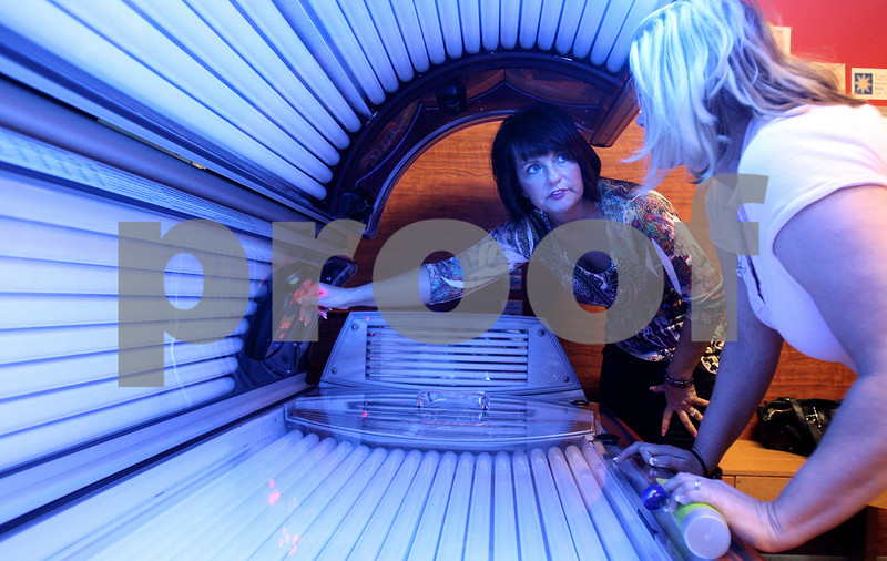 """Kyle Bursaw – kbursaw@daily-chronicle.com<br /> <br /> Dynamic Tanning co-owner Teresa Lynch, explains how to use a tanning bed called """"The Race"""" to Tara Kraabel prior to her using it at their Sycamore road location in DeKalb, Ill. on Tuesday, March 8, 2011. Kraabel is a returning customer, but had not previously used that type of bed."""
