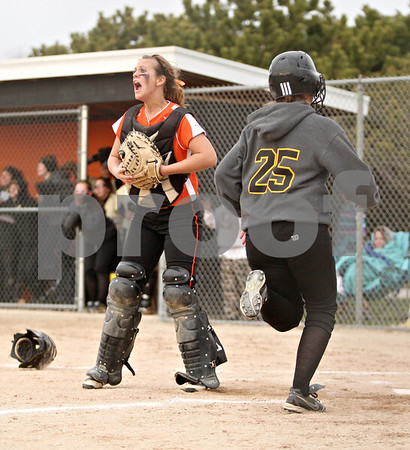 Rob Winner – rwinner@daily-chronicle.com<br /> <br /> DeKalb's Alysha Guy calls for the ball as Sycamore's Meranda Brashears crosses home during the seventh inning on Tuesday, April 5, 2011, in DeKalb, Ill. DeKalb defeated Sycamore, 4-3.