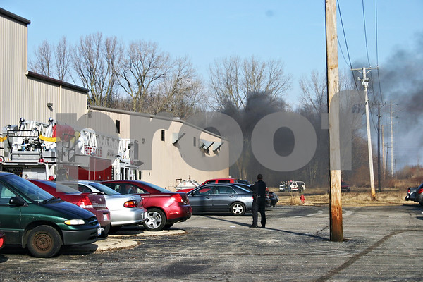 ANDREW MITCHELL – amitchell@shawmedia.com<br /> A DeKalb police officer watches Monday as smoke rises from the northeast corner of the Tegrant building in DeKalb.  Offical said an electrical transformer exploded and set fire to a parked semi-trailer and part of the building.