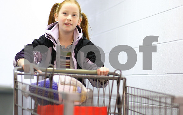 Kyle Bursaw – kbursaw@shawmedia.com<br /> <br /> Abigail Lewis, 10, runs a shopping cart with a turkey and a bag of other food to the entrance of the Salvation Army in DeKalb where recipients of the meal packages were waiting on Tuesday, Nov. 22, 2011.