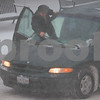 Kyle Bursaw – kbursaw@daily-chronicle.com<br /> <br /> A passenger tries to free the windshield wipers on a van while at a stoplight on Lincoln Highway on Tuesday, Feb. 1, 2011.