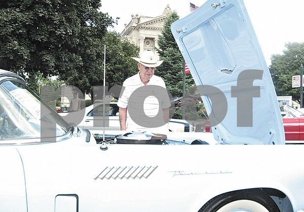 Duane Stevenson, of St. Charles, looks over a powder blue 1957 Ford Thunderbird during the Fizz Ehrler Memorial Car Show in downtown Sycamore on Sunday.