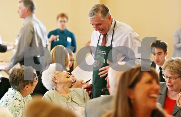 """Rob Winner – rwinner@daily-chronicle.com<br /> <br /> Sycamore Vera Anderson (left) speaks to state Representative Bob Pritchard, who was serving croissants and coffee, during the fourth annual """"Meals for Moms"""" luncheon hosted by the Voluntary Action Center at the Regale Center in Sycamore on Monday afternoon."""