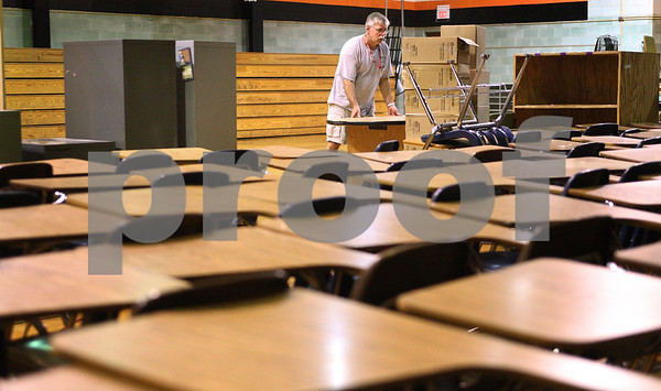 Kyle Bursaw – kbursaw@daily-chronicle.com<br /> <br /> Ray Faivre moves furniture into a gymnasium at Huntley Middle School, on Seventh Street on Tuesday, June 7, 2011.