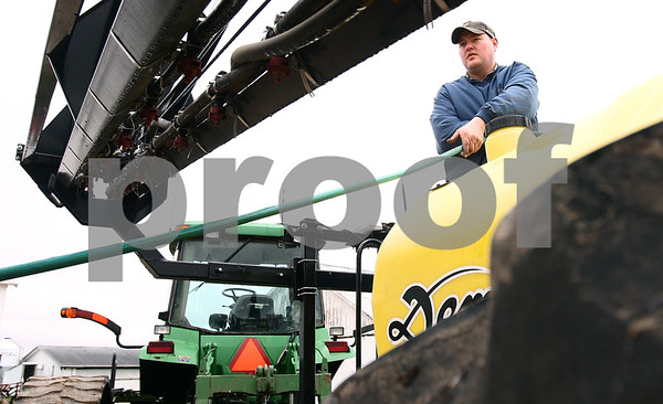 Kyle Bursaw – kbursaw@daily-chronicle.com<br /> <br /> Mike Schweitzer pulls a line of hose up to the tank of a sprayer, which he was doing maintenance on at his farm in Esmond, Ill. on Wednesday, April 27, 2011 because it was too wet and cold to start planting.