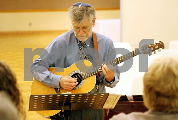 Rob Winner – rwinner@shawmedia.com<br /> <br /> Choir director Harvey Blau practices the guitar before a Rosh Hashanah service at the Northern Illinois University Holmes Student Center in DeKalb on Wednesday, Sept. 28, 2011.