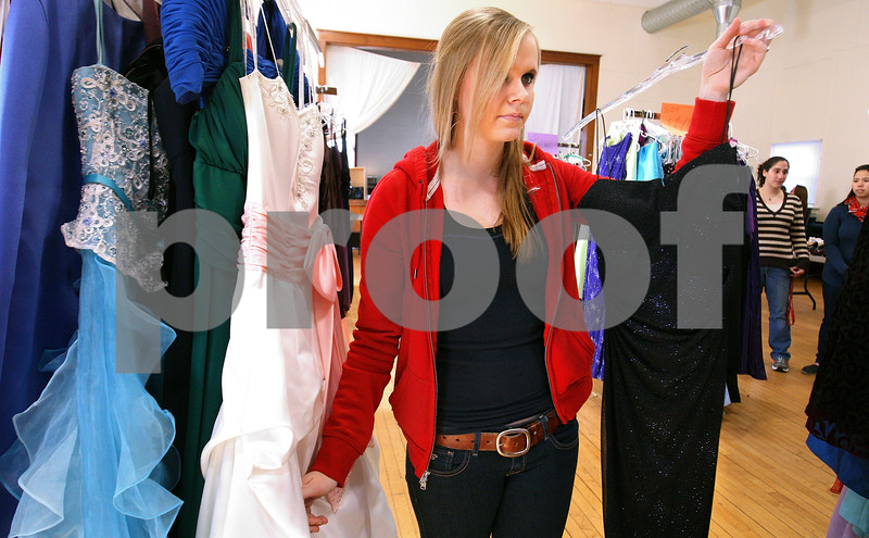 Kyle Bursaw – kbursaw@daily-chronicle.com<br /> <br /> Emma Floit, a junior at Sycamore high school, having trouble choosing between two dresses she likes holds up one to her mom, Kathy Floit (not pictured), to get input as they search for a dress at Project Prom on Saturday, Feb. 19, 2011. Project Prom is at Conexion Comunidad in DeKalb, Ill. and will also be going on Sunday from 1-5.