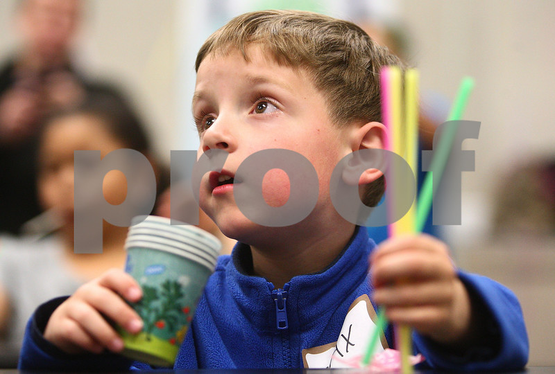 Kyle Bursaw – kbursaw@daily-chronicle.com<br /> <br /> Max Hove, 6, looks to the adults for help making anemometer, a device which measures wind speeds, out of cups and straws during an activity at the meteorology and geography kid's day in Davis Hall at NIU on Saturday, May 7, 2011.
