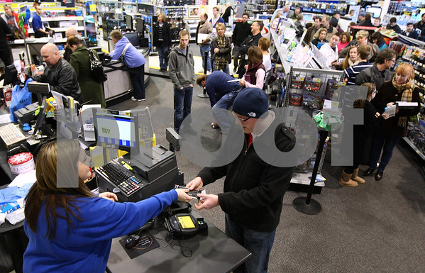 Kyle Bursaw – kbursaw@shawmedia.com<br /> <br /> Kathy Ciurus (bottom left), a back office lead at Best Buy in DeKalb, completes an exchange of a cell phone case for a customer on Monday, Dec. 26, 2011.