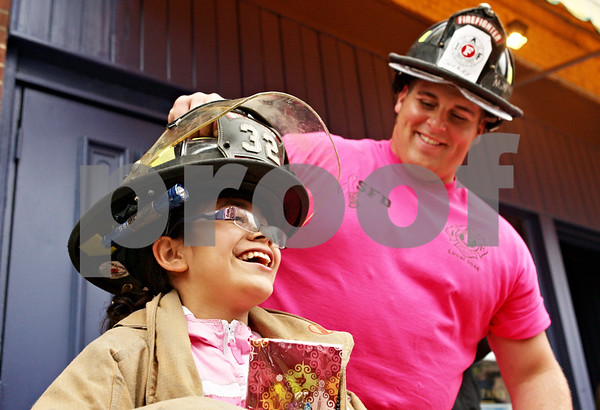 Rob Winner – rwinner@daily-chronicle.com<br /> <br /> Sycamore resident Andrea Covarrubias, 9, tries on a firefighter helmet and jacket with the help of Adam Honiotes of the Sycamore Fire Department during Sycamore's Ladies Night Out on Thursday evening. The annual event raises money for breast cancer research.