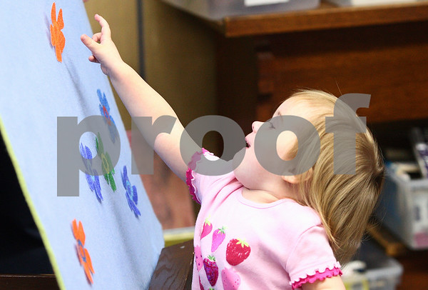 Kyle Bursaw – kbursaw@daily-chronicle.com<br /> <br /> Maggie Squier places an orange flower made of paper onto a board during an activity meant to help young children learn the names of colors. The exercise was part of toddler time at DeKalb Public Library on Wednesday, April 13, 2011.
