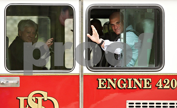 Rob Winner – rwinner@daily-chronicle.com<br /> <br /> United States Marine Corps. Cpl. Kyle LeJeune (right) and his father Glenn wave from a Sandwich fire engine before a gathering at the Timber Creek Inn and Suites in Sandwich on Tuesday afternoon.<br /> <br /> ***Images are RGB. Please convert to CMYK and use the Print Sharp action on Photoshop. Ask Kyle or Curt if you don't understand please. -Rob***